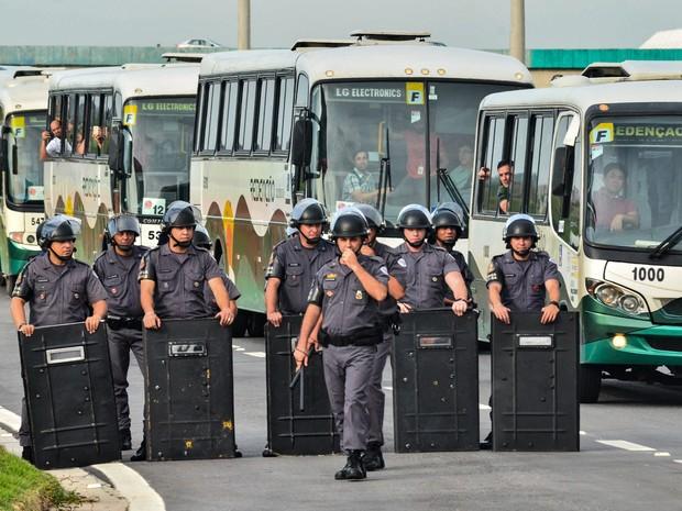 Policiais militares acompanham a entrada de funcionários que não aderiram à greve da LG em Taubaté, no interior de São Paulo, na manhã desta sexta-feira (11). Os trabalhadores completam uma semana de paralisação hoje (Foto: Nilton Cardin/Estadão Conteúdo)