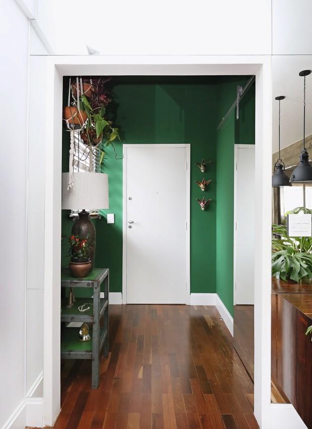 Hall de entrada. As paredes ganharam o tom vibrante Doce de Mamão, da Suvinil. A estante baixa é do estúdio Meji Design (Foto: Mariana Orsi / Editora Globo)