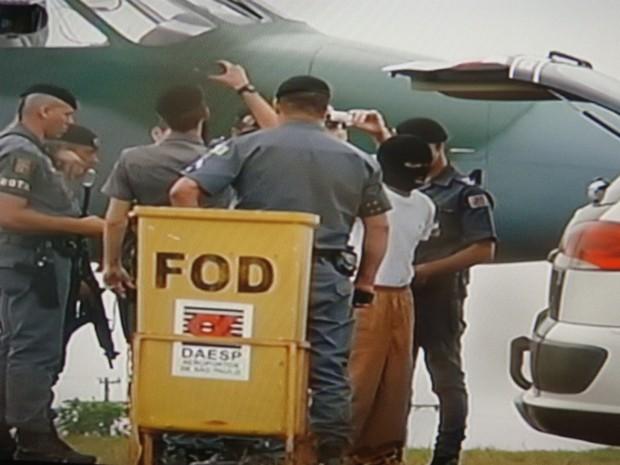Preso ficou encapuzado até a entrada no avião da Força Aérea Brasileira. (Foto: Reprodução TV Tem)