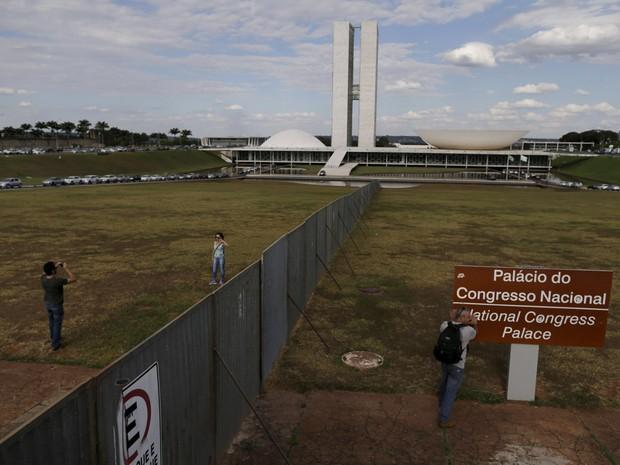 Pessoas são vistas perto do alambrado em frente ao Congresso Nacional, em Brasília, instalado para dividir os manifestantes pró e contra o impeachment da presidente Dilma Rousseff. A votação do impeachment está prevista para domingo (17) (Foto: Ueslei Marcelino/Reuters)
