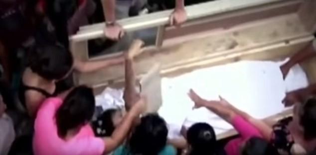 Pessoas tentam 'reanimar a morta' (encenação)