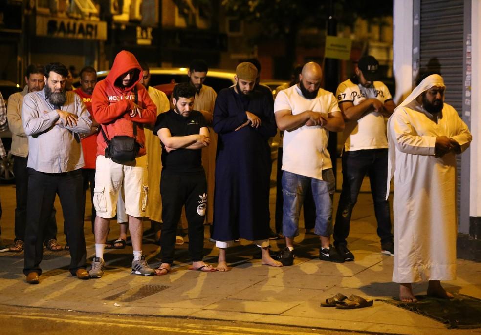 Homens oram após motorista atropelar pessoas em frente a mesquita em Finsbury Park, no norte de Londres (Foto: Neil Hall/Reuters)