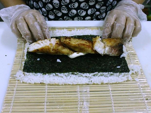 Cubra a alga com arroz e vire para incluir o cream cheese e o peixe ao centro (Foto: Leandro Tapajós/G1 AM)