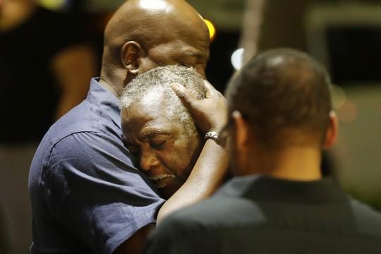 Fiéis se consolam após crime na Emanuel African Methodist Episcopal Church, na Carolina do Sul, EUA. Atirador branco matou 9 pessoas em igreja da comunidade negra (Foto: David Goldman/AP)