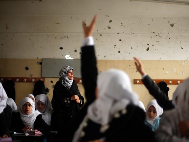 Estudantes palestinas assistem a uma aula em escola que testemunhas dizem ter sido atingida por um bombardeio israelense durante o mais recente conflito entre Israel e o Hamas, em um dia chuvoso no leste da Cidade de Gaza  (Foto: Suhaib Salem/Reuters)
