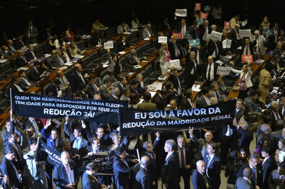 Deputados contra e a favor da redução da maioridade penal levantam cartazes no plenário (Foto: Fabio Rodrigues Pozzebom/Agência Brasil)
