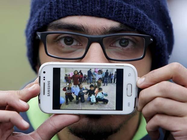 Basas, de Damasco, exibe foto de crianças com as quais trabalhava como voluntário na Síria (Foto: REUTERS/Srdjan Zivulovic)