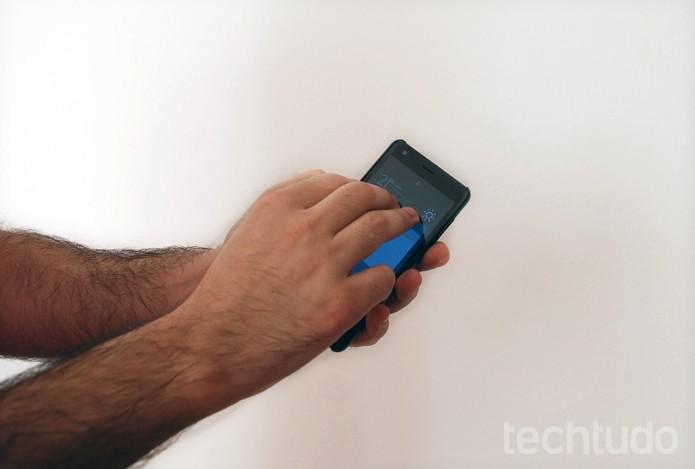 Três dedos posicionados na parte superior do Redmi 2 (Foto: Raquel Freire/TechTudo)