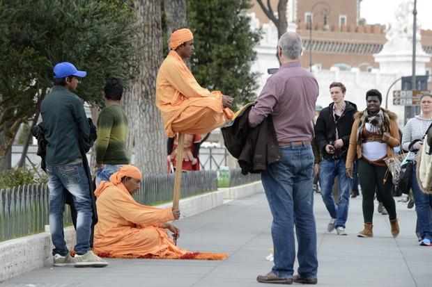 Por meio de truque, artista parece segurar homem com apenas uma haste de madeira (Foto: Andreas Solar/AFP)