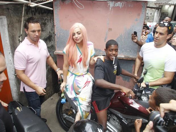 8 de novembro - Lady Gaga posa para foto ao lado de um garoto em uma moto na comunidade do Cantagalo (Foto: Delson Silva/AgNews)