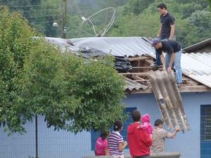 Moradores substituem telhas e utilizam lonas para proteção (Foto: Reprodução/RBS TV)