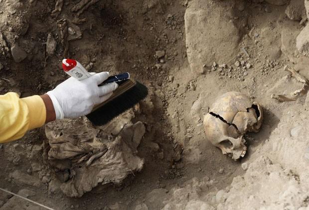 Arqueólogo trabalha na limpeza dos restos mortais encontrado em Lima, no Peru (Foto: Mariana Bazo/Reuters)