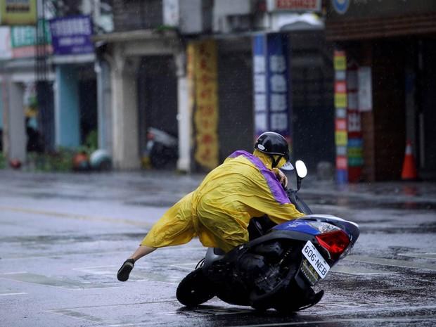 Motociclista escorrega e toma um tombo com sua moto no asfalto molhado enquanto o tufão Megi passa por Hualien, no leste de Taiwan (Foto: Tyrone Siu/Reuters)