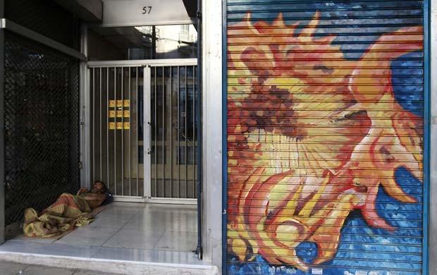 Grego sem-teto dorme em entrada de prédio para alugar no centro de Atenas nesta segunda-feira (18) (Foto: AFP)