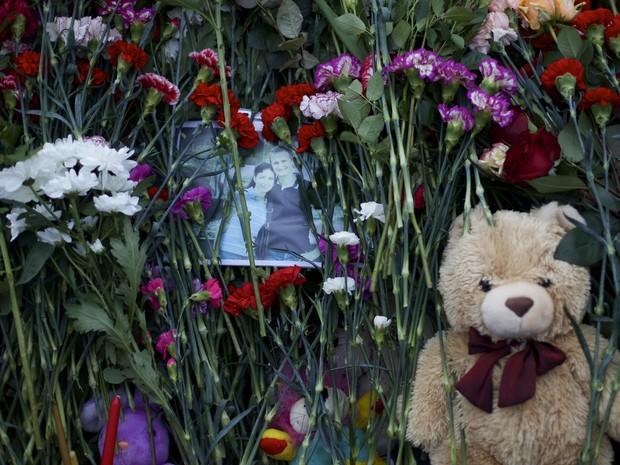 Foto de vítimas do acidente com o avião russo da companhia Metrojet ao lado de flores e objetos colocados como homenagem (Foto: Ivan Sekretarev/AP)