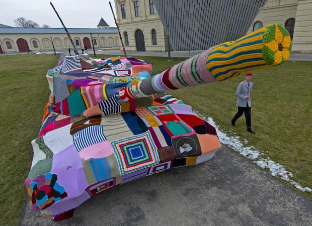 Major alemão Sebastian Bundeswehr olha para o tecido de malha que cobre um tanque em frente ao Museu de História Militar em Dresden, na Alemanha, nesta segunda-feira (11). (Foto: Robert Michael/AFP)