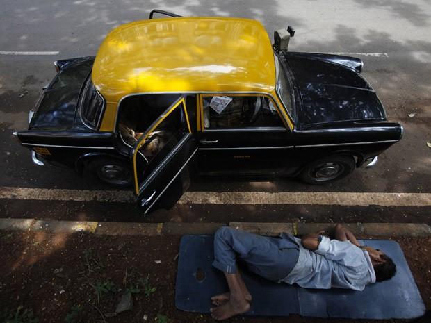 Taxista dorme ao lado de seu Premier Padmini estacionado em rua de Mumbai, na Índia  (Foto: Vivek Prakash/Reuters)