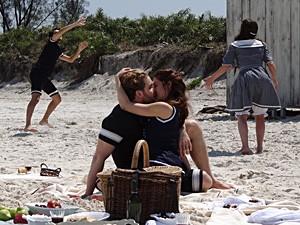 Laura e Edgar curtem o dia na praia (Foto: Lado a Lado / TV Globo)