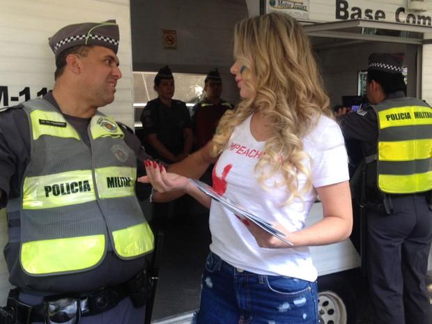 SÃO PAULO: A socialite Ju Isen conversa com policial militar na Avenida Paulista e oferece sua revista (Foto: Isabela Leite/G1)