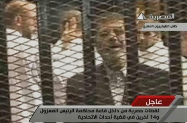 O presidente deposto do Egito, Mohamed Morsi, aparece no tribunal nesta segunda-feira (4), em imagem divulgada pela TV estatal. (Foto: AFP)