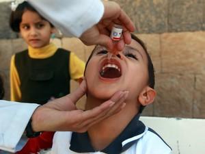 Um médico administra uma vacina contra a poliomielite em uma criança em um centro de saúde de Sanaa, capital do Iémem. O governo informou que a campanha nacional tem como alvo 11.589.887 crianças e adolescentes entre 9 meses e 15 anos (Foto: Mohammed Huwais/AFP)