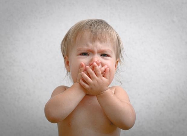Bebê chorando com a mão na boca (Foto: Thinkstock)