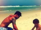 Juliano Cazarré brinca com o filho na areia da praia
