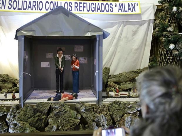 Mulher tira foto de presépio com menino Aylan em igreja de Madri, na Espanha (Foto: REUTERS/Andrea Comas)