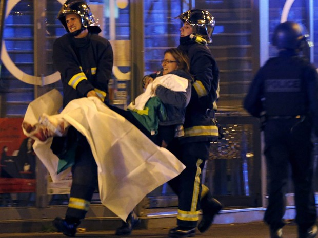 Mulher é socorrida após tiroteio perto do Bataclan, conhecida sala de espetáculos de Paris, na França (Foto: Christian Hartmann/Reuters)
