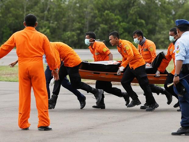 31/12 - Equipes de resgate descarregam o corpo de uma das vítimas do voo da AirAsia nesta quarta-feira (31) (Foto: Achmad Ibrahim/AP Photo)