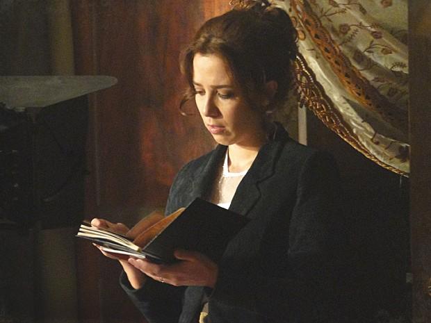 Laura fica incomodada ao ver a foto de outra mulher nas coisas de Edgar (Foto: Lado a Lado / TV Globo)