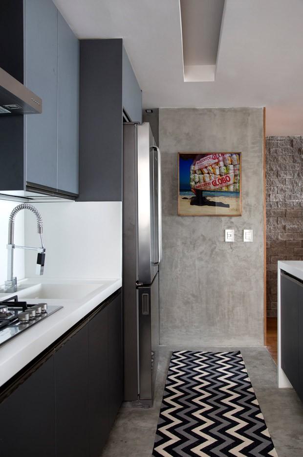 A cozinha com 9 m² ganhou piso e paredes de cimento queimado, à venda na Triplex.  Os armário em melamina cinza e a bancada da pia de corian, são da Florense Ipanema. Torneira gourmet da Deca. Tapete da LZ Studio (Foto: Denílson Machado - MCA Estúdio/Divulgação )