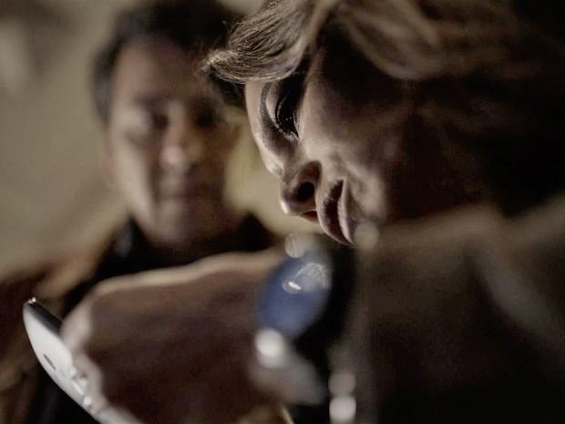 Rosa e Pedroso conseguem um carregador e tentam fazer o celular funcionar (Foto: O Rebu / TV Globo)