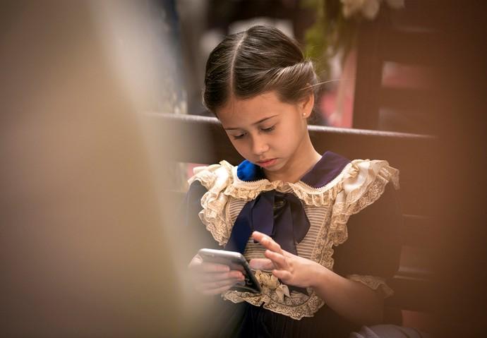 A pequena Nathalia Costa se diverte no celular durante um intervalo na gravação (Foto: Isabella Pinheiro/Gshow)