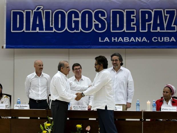 O chefe da equipe de negociação do governo colombiano Humberto de la Calle, na frente à esquerda, cumprimenta Ivan Marquez, negociador-chefe das Farc nesta terça-feira (15) em Havana (Foto: AP Photo/Ramon Espinos)