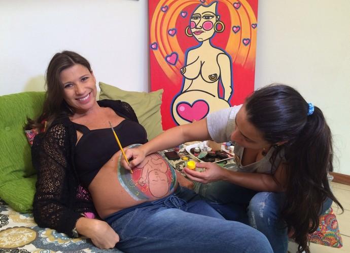Camille Reis mostra a pintura na barriga de gestantes (Foto: RBS TV/Divulgação)