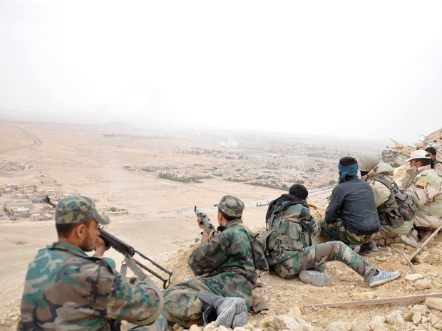 In this photo released by the Syrian official news agency SANA, Syrian soldiers take up positions during fighting between Government forces and Islamic State group militants in Palmyra, Syria, Sunday, March 27, 2016. Syrian state media and an opposition m (Foto: SANA/AP)