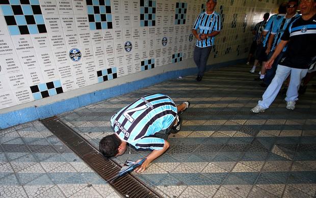 Torcedor beija o chão do Olímpico na tarde que marca a despedida (Foto: Lucas Uebel/Grêmio FBPA)