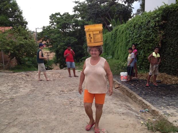 A dona de casa Francisca Maria, 60 anos, carrega balde de água na cabeça (Foto: Jaqueliny Siqueira/G1)