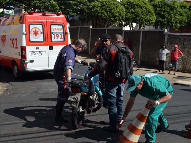 Funcionário do Samu e guarda municipal ajudam a retirar moto da rua no Centro de Ribeirão Preto, SP (Foto: Clayton Castelani/ G1)