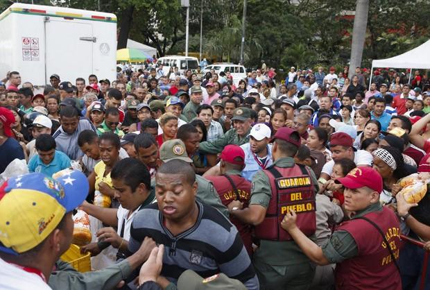 Soldados venezuelanos tentam controlar a multid�o que quer comprar frangos no mercado estatal Mega-Mercal neste s�bado (24) (Foto: Reuters/Carlos Garcia Rawlins )