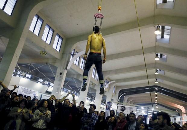 Juan Pablo Diaz fica suspenso com ganchos cravados no corpo (Foto: Rodrigo Garrido/Reuters)