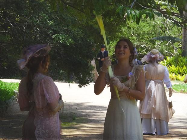 Alice amarra a fita na árvore (Foto: Lado a Lado/TV Globo)