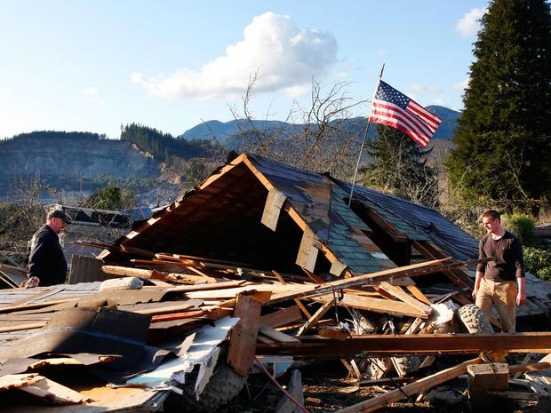 Homens procuram pertences em casa destruída perto de Oso, Washington. Deslizamento de terra nos EUA deixa pelo menos 8 mortos (Foto: Genna Martin/The Herald/AP)