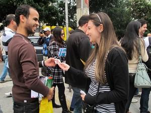 Giovanna entrega santinho para candidato ao exame da OAB (Foto: Rafael Sampaio/G1)
