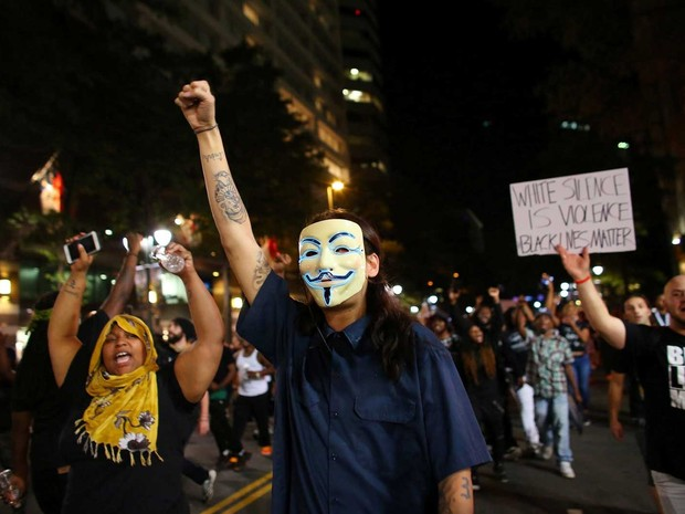 Manifestante usa máscara durante protesto em Charlotte (Foto: Mike Blake / Reuters)