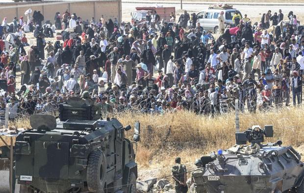 Refugiados sírios fugindo da cidade de Tal Abyad pedem água na fronteira com a Turquia neste domingo (14) (Foto: Bulent Kilic/AFP)