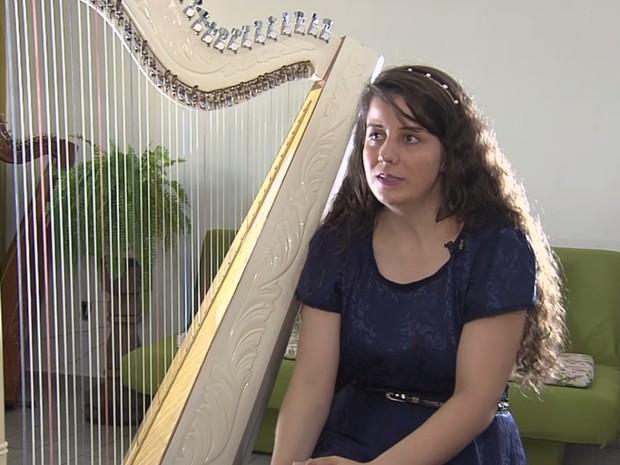 Jovem se tornou uma das poucas harpistas de Goiânia após ser adotada por cantora Goiás (Foto: Reprodução/TV Anhanguera)
