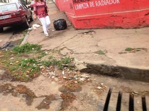 Pedestre desvia de buracos em calçada no Bairro Porto Velho (Foto: Ricardo Welbert/G1)