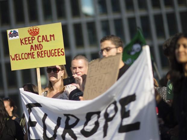 """Participante de manifestação pró-migrante mostra cartaz """"mantenha a calma e acolha os refugiados"""" em Potsdamer Platz, em Berlim, neste sábado (Foto: AFP PHOTO/AXEL SCHMIDT)"""